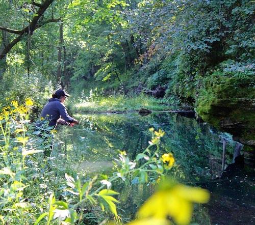 Laurel Monaghan fishing on a river