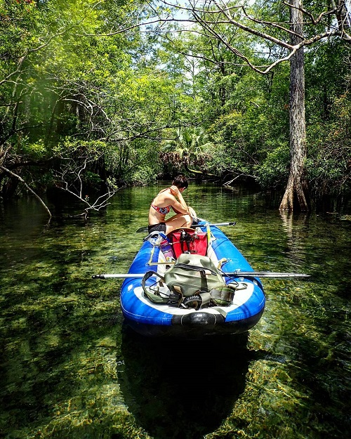 women on a raft in a swampy area with vibrant tress around and a drybag in the boat