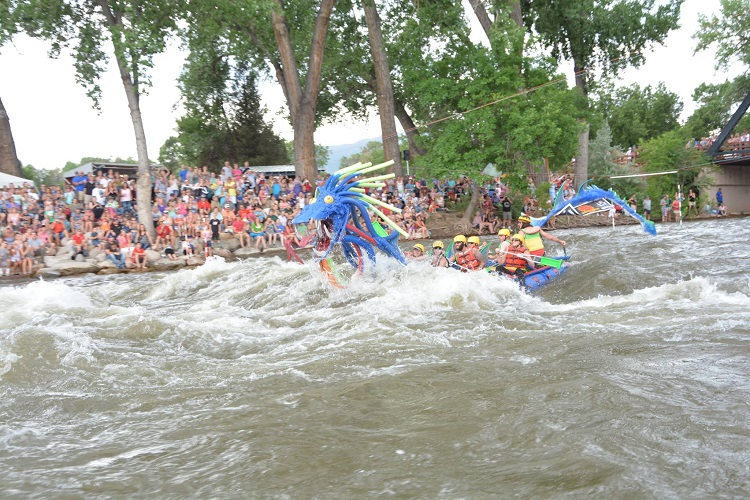 Dragon raft floating down the river as people cheer on the sideline, image from Royal Gorge Whitewater Festival