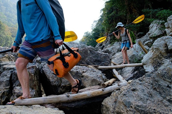 Person carrying a watershed drybag to the water carrying a paddle photo by bradengunem