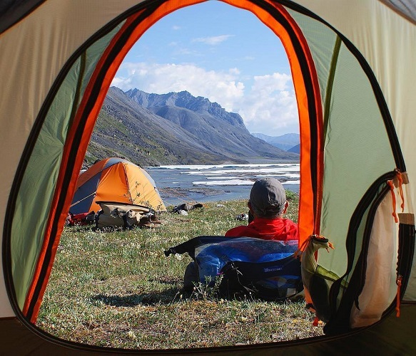 view from a tent with a mountain and lake view