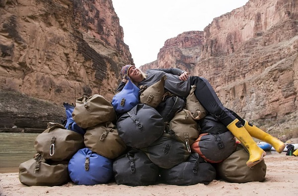 Women laying on top of many drybags outside image by tom_attwater_media