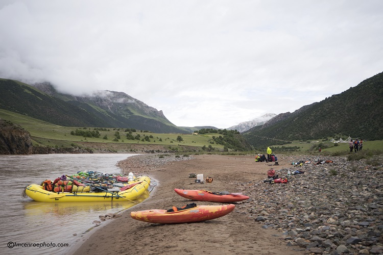 Rafts, Kayaks and Watershed Drybags parked on the shore in the mountains of Tibet