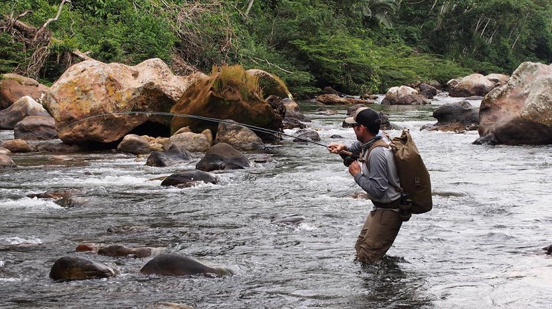 Man fishing in the river with the water knee level wearing a Big Creek Drybag