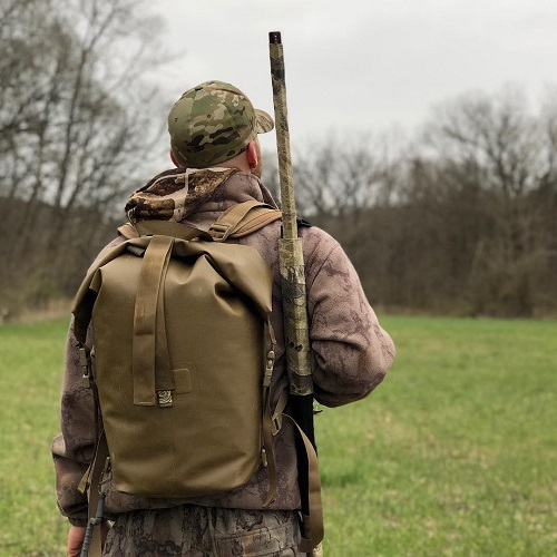 Man with an Animas Watershed Drybag on wearing all camo and a gun on his shoulder