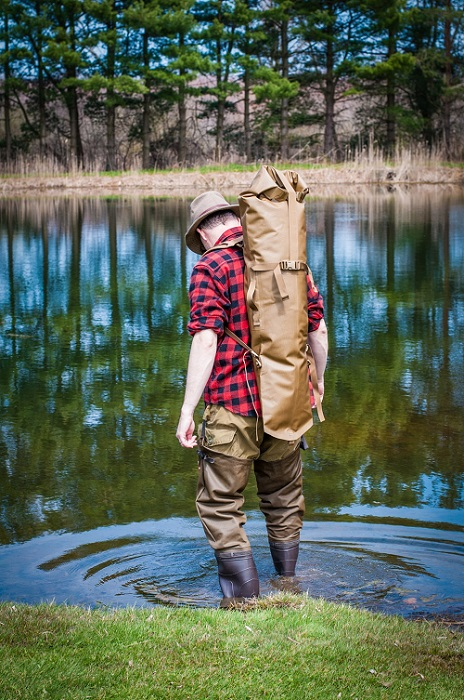 Man wearing a Rangeland™ Long Gun Backpack and stepping into a pond of water