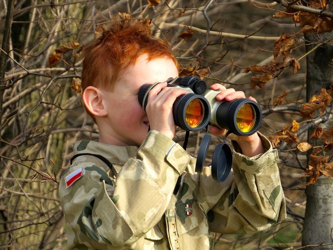 Person holing binoculars wearing camo attire in the woods.
