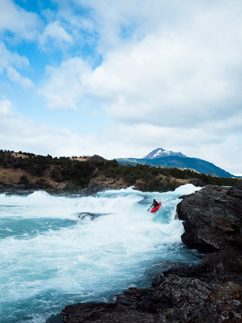 Photo by Dylan McKinney in Patagonia kayaking down the blue river with a mountain peak in the background