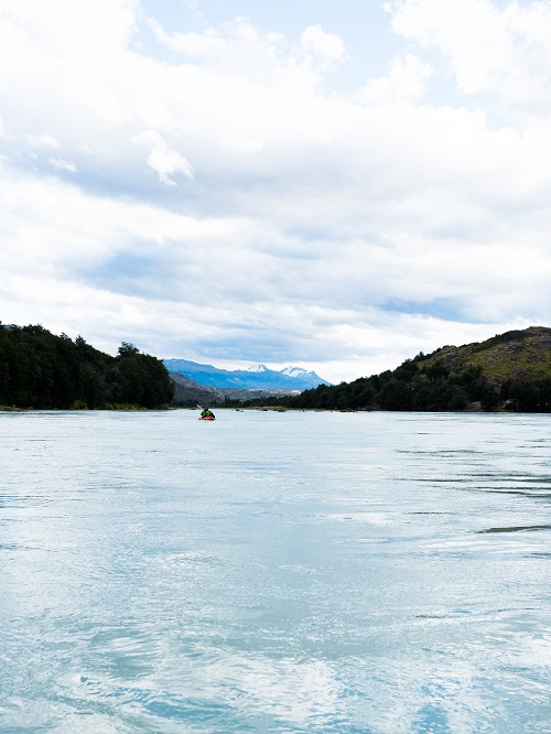 Kayaker in the middle of a calm river with some mountain peaks in the background