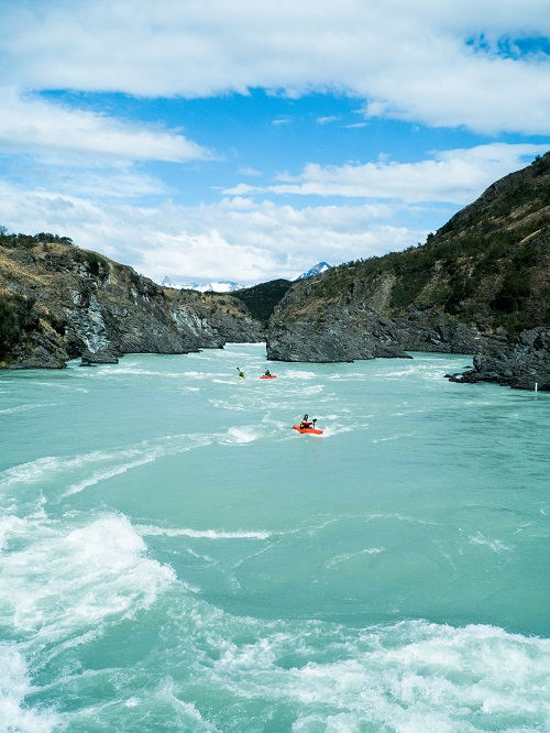 Photo by Dylan McKinney in Patagonia kayaking down a blue river with a blue sky overhead