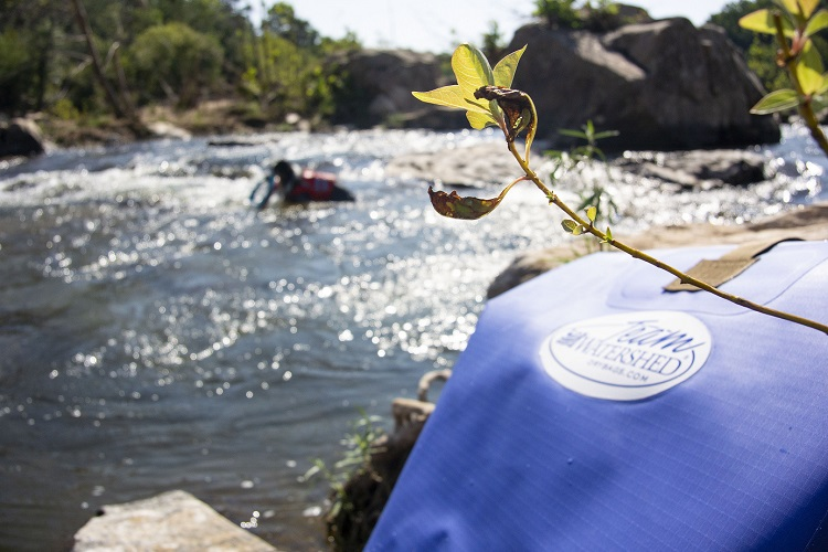 Team Watershed logo on the backpack in the water