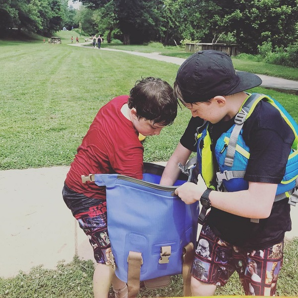 Two kids reaching into a Watershed Drybag for snacks