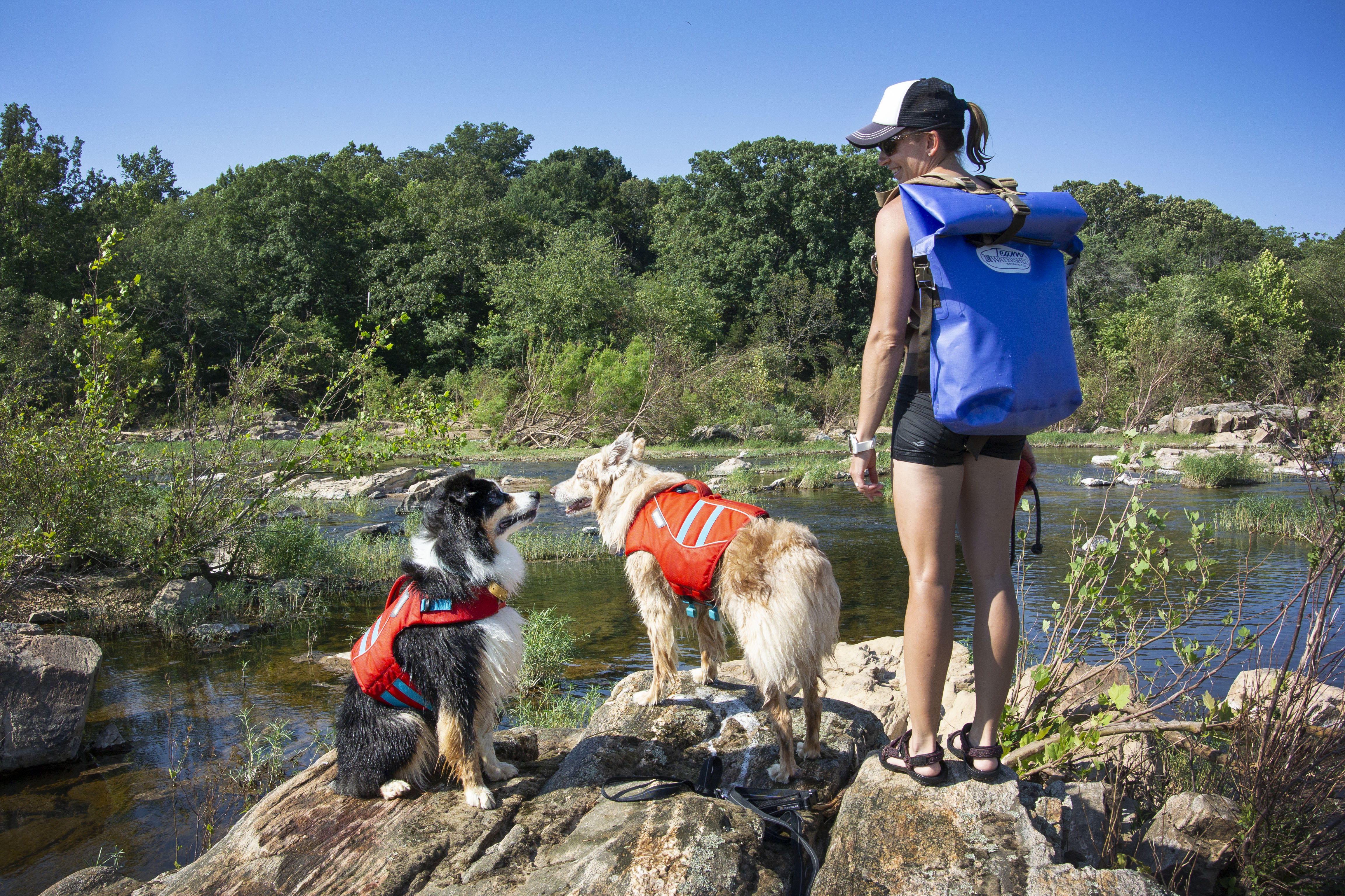 Women with a Watershed drybag backpack on and two dogs standing next to her by the river