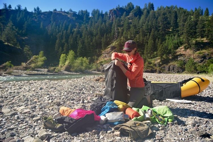 Packing an Animas backpack with clothes and necessities on the bank of the river