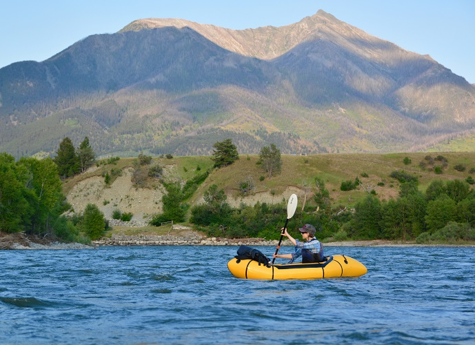 Paddling on blue waters with a mountain in the background
