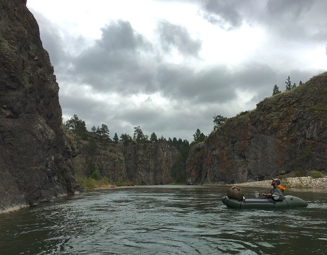 Paddling in a raft up to steep canyons