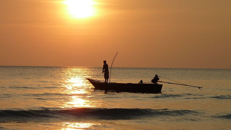 Two people fishing off a boat in the ocean while the sun sets.