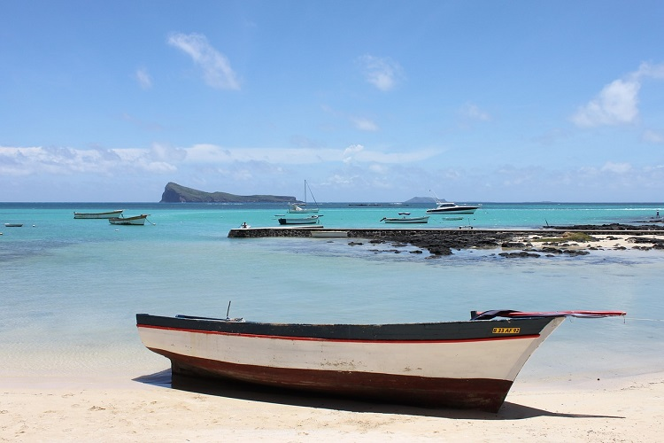 Fishing boat sitting on the sandy shore next to crystal blue water
