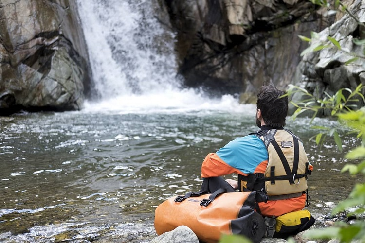 Man sitting on a rock with his PDF on and a Watershed Drybag next to him watching a waterfall