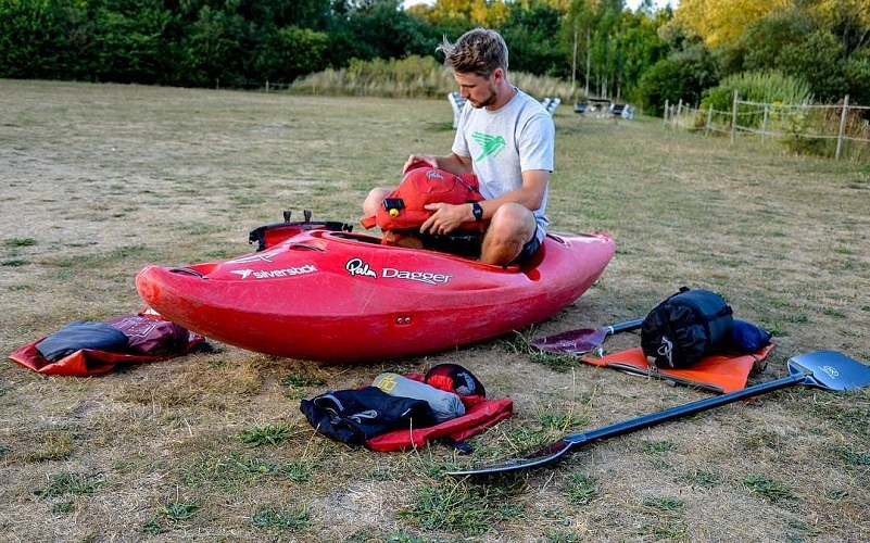 Man sitting in a kayak on dry land packing his drybag for the day