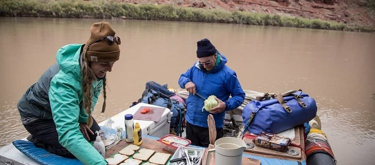 Two people preparing lunch on a raft