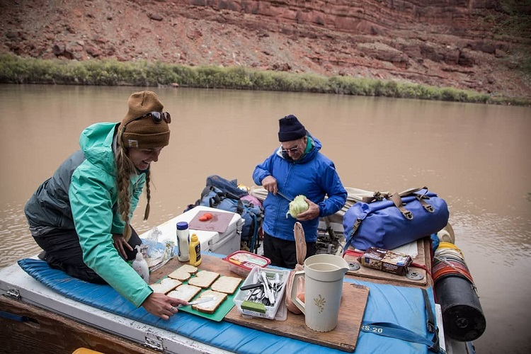 Two people making lunch on a raft with a Watershed Drybag in the picture