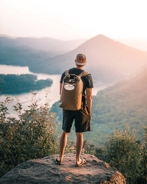 Man wearing an Animas backpack while overlooking a river