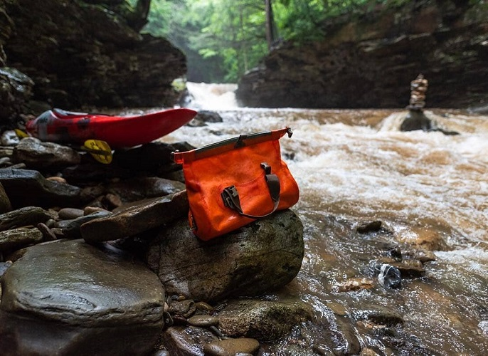 Ocoee Drybag sitting on a rock next to the river with a kayak in the background