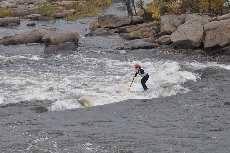 Person paddling down some whitewater on a SUP board