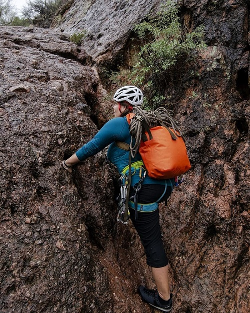 Rock climber with a Watershed Drybags backpack on scaling a wall