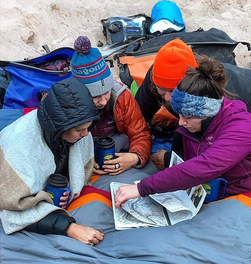Four people huddled over a map outside wearing winter gear
