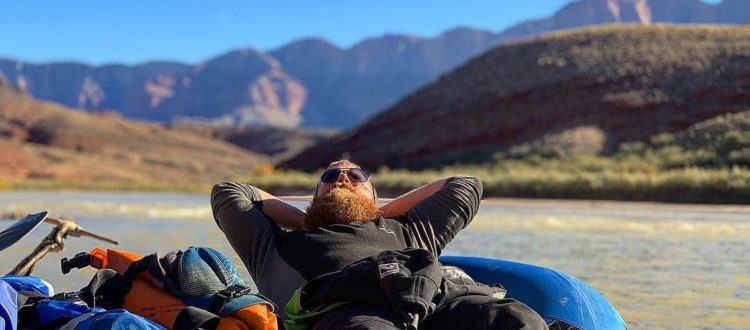 Man relaxing on a raft as he floats down the river with canyons in the background