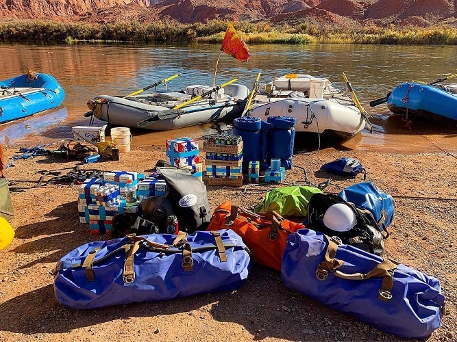Watershed Drybags by some rafts next to the river in a canyon